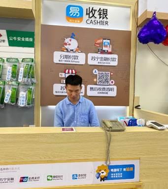 (图:张拓铭在门店收银台)