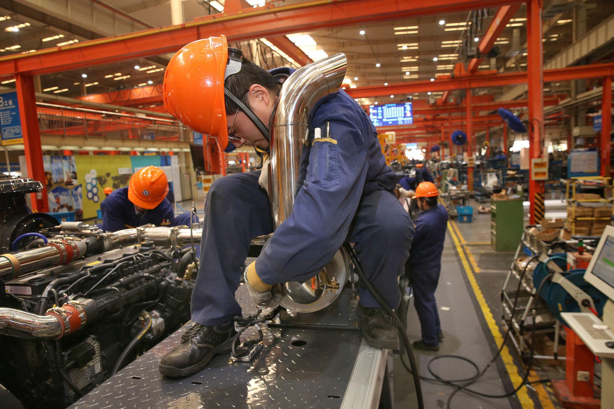 江苏徐州,工作人员在组装工程机械| 人民视觉