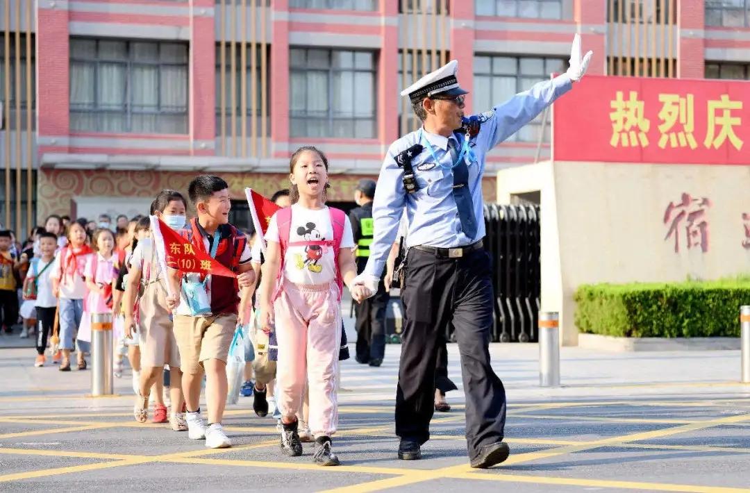 △宿迁辅警护送学生过马路