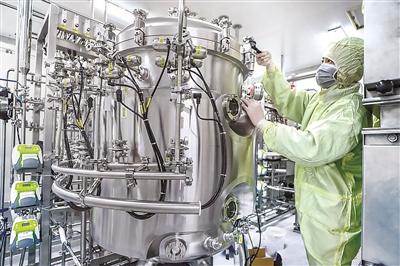 防护严密的工作人员在北京生物制品研究所新冠灭活疫苗生产车间工作。(图片来源:国药集团)
