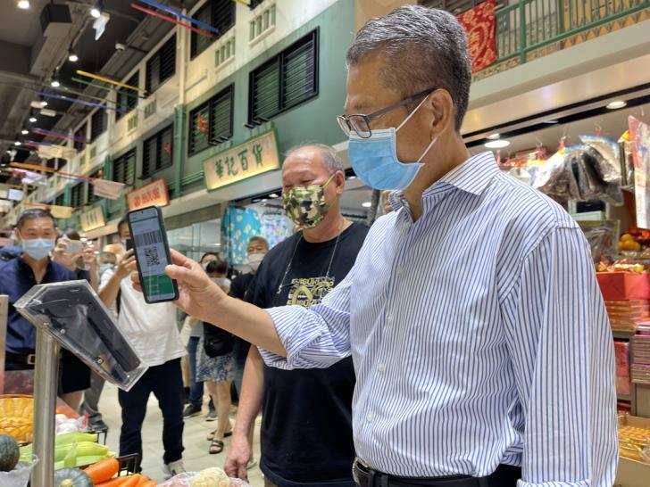 (香港特区政府财政司司长陈茂波在香港街市了解电子支付消费情况。特区政府供图)
