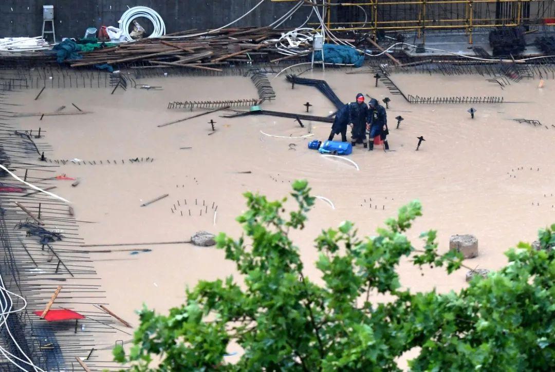 △7月20日,工作人员在郑州市一建筑工地排水。(图源:新华社)