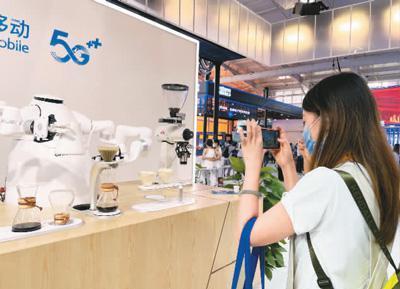 """服贸会电信、计算机和信息服务专题展上,观众在参观中国移动带来的可以制作手冲咖啡的""""AI咖大师""""。本报记者 徐佩玉摄"""