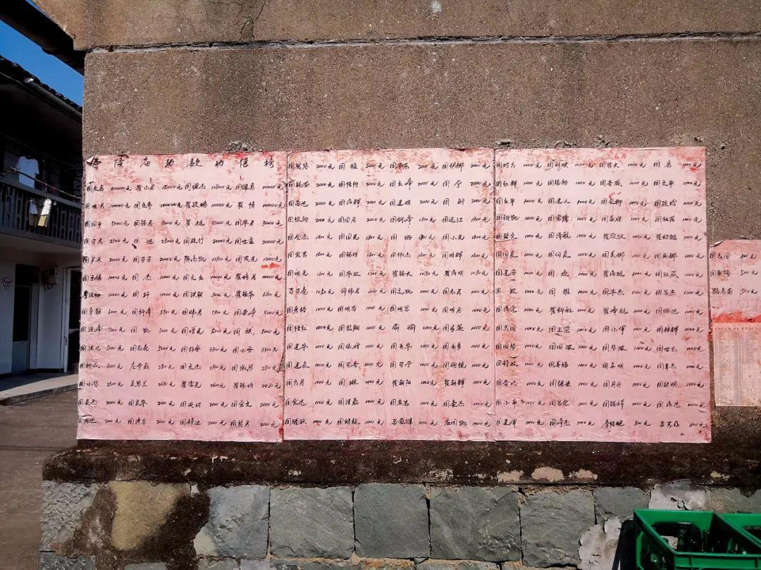 """章溪村中多处张贴着""""寿隆庙助款功德榜"""",周文勇名字排在第一位。摄影/本刊记者 周群峰"""
