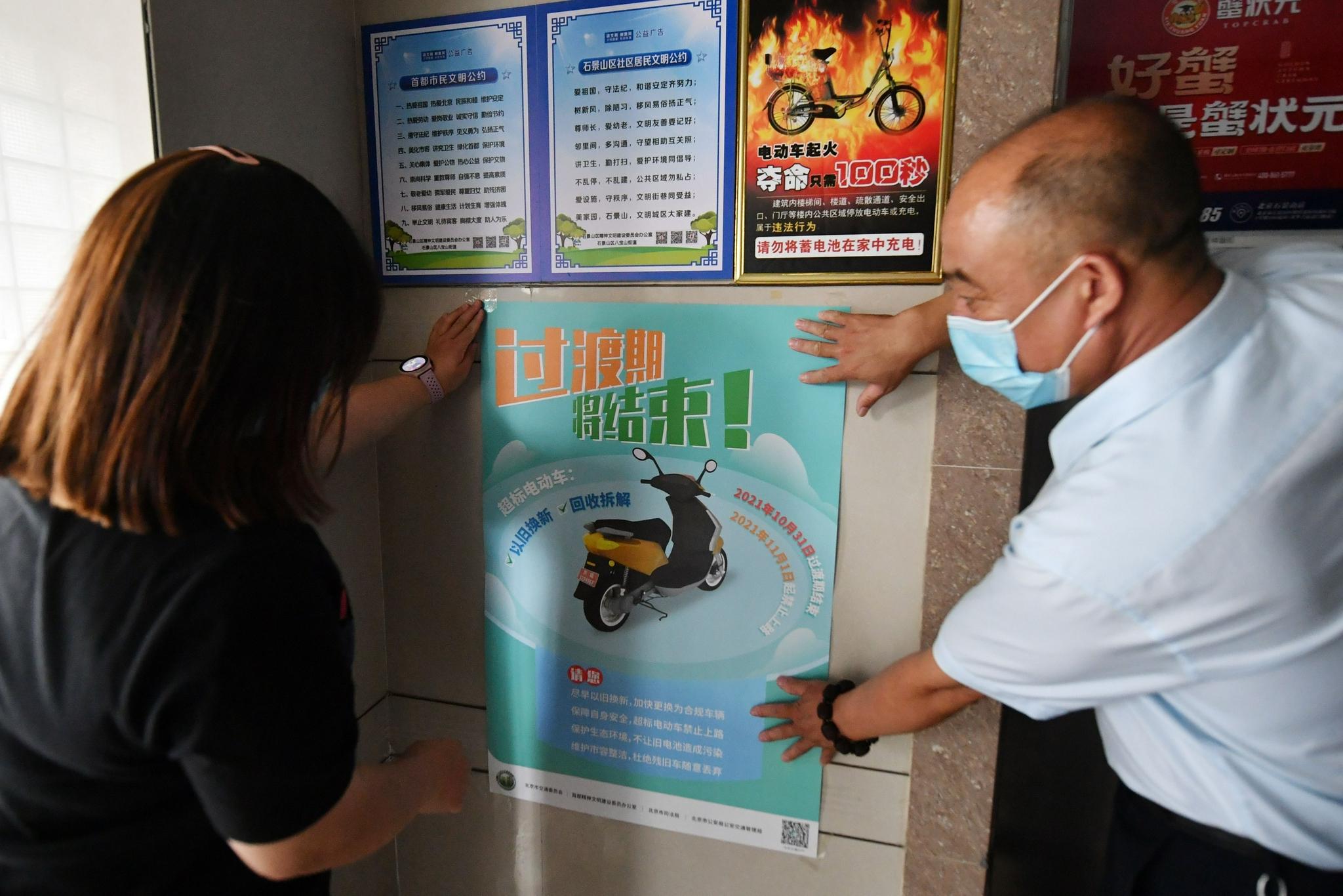 工作人员在居民楼里贴超标电动车过渡期将结束提示牌。新京报记者 王贵彬 摄