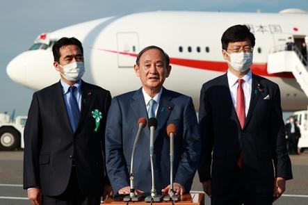 菅义伟23日在羽田机场接受记者采访