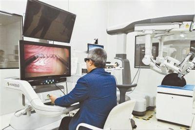 工作人员体验苏州康多研发的国产腹腔镜手术机器人。   苏州高新区供图