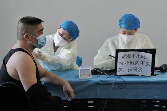 △1月10日,北京市东城区和平里街道一处疫苗接种点,北京公交公司的公交车驾驶员接种新冠疫苗。
