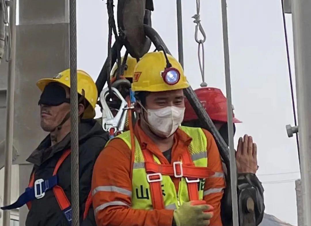 获救矿工戴着黑色眼罩升井后,一人双手合十向救援人员感谢。图片来源:烟台市委宣传部