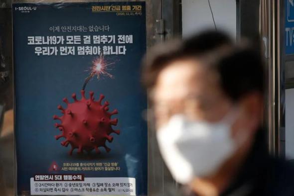 ↑别名戴口罩的外子走过韩国首尔一处宣传抗疫的海报图据韩国日本的一级片