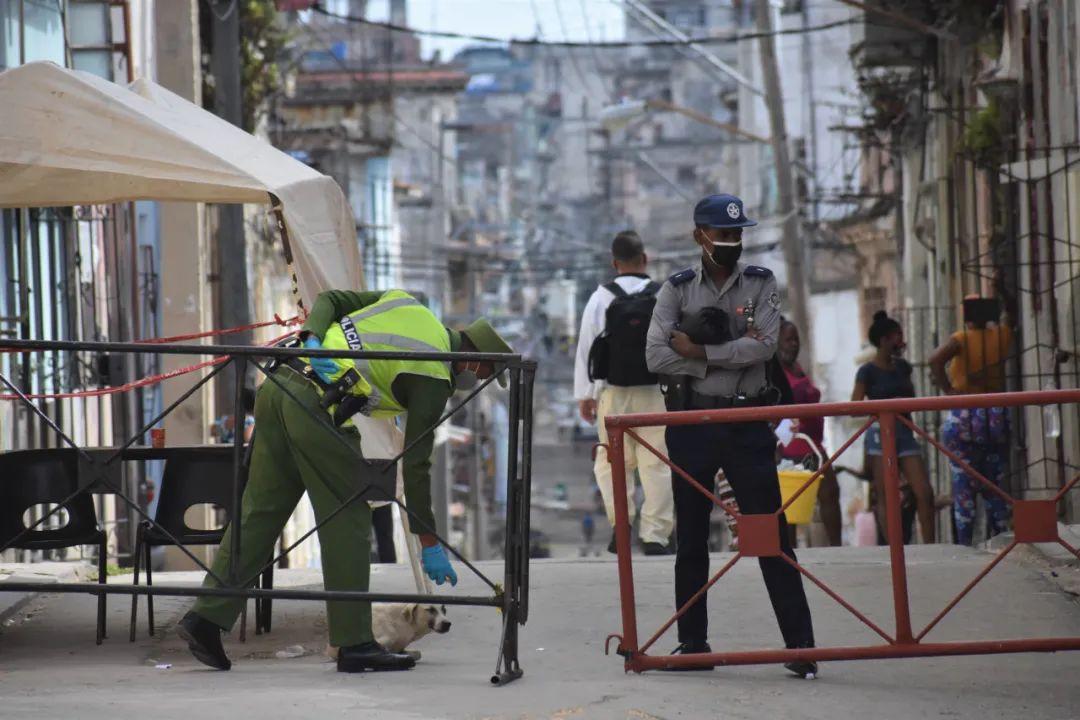 2月5日,警察在古巴哈瓦那一处因出现疫情而限制出入的街区内执勤。新华社记者朱婉君摄