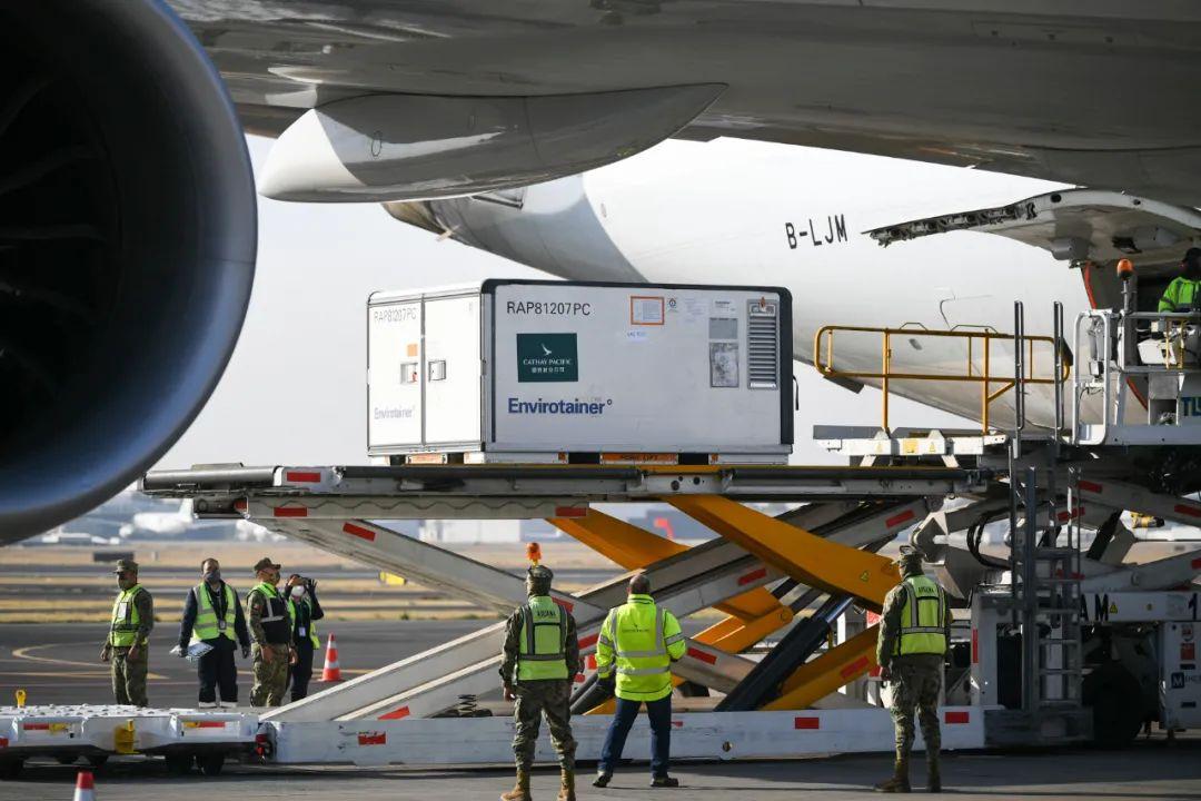 2月20日,在墨西哥首都墨西哥城国际机场,工作人员从飞机上卸下装有中国科兴新冠疫苗的温控集装箱。新华社记者辛悦卫摄