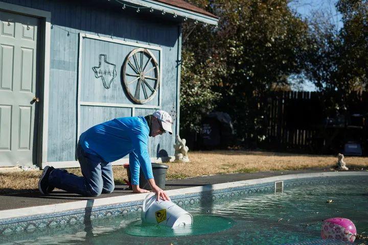 2月20日,在美国得克萨斯州矿泉井城,一名男子在自家泳池内打水为马桶蓄水。新华社/路透