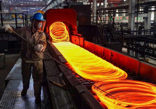 河北省迁安市一家精品钢生产企业的工人在钢筋生产线上工作。(杨世尧 摄)