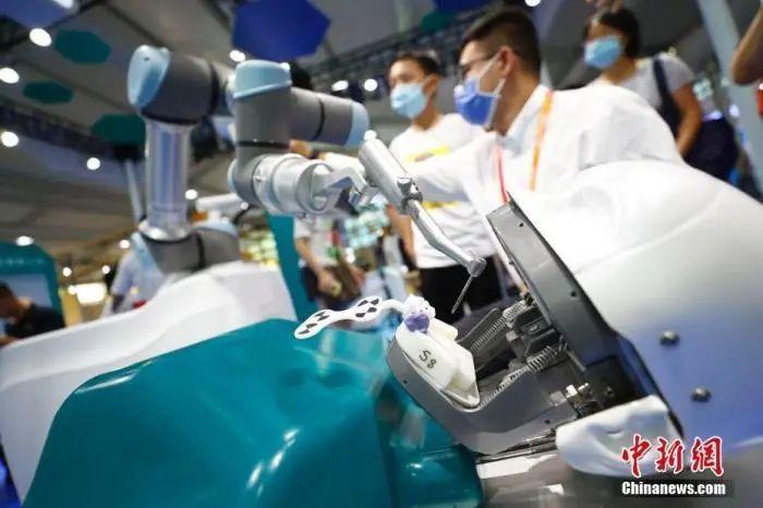 ↑资料图:在2020年服贸会服务机器人专题展区,口腔种植手术机器人吸引参观者。中新社记者 富田 摄
