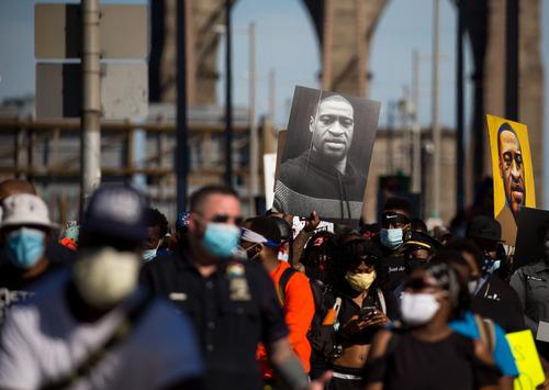 2020年6月13日,抗议者手举弗洛伊德的肖像通过美国纽约布鲁克林大桥。新华社发