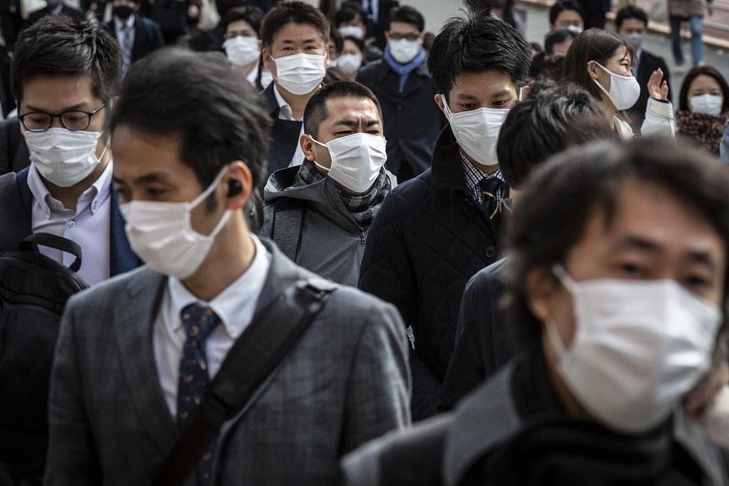 资料图:日本市民佩戴口罩出行