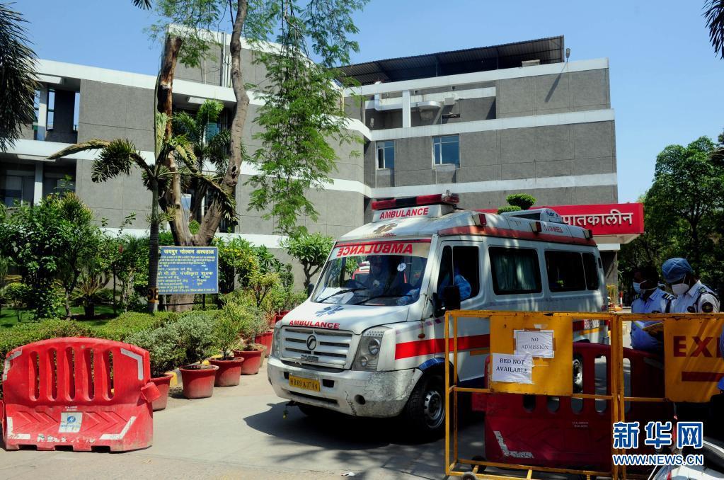 """4月24日,救护车驶过印度新德里一家门口贴着""""没有床位""""告示的医院。新华社发"""