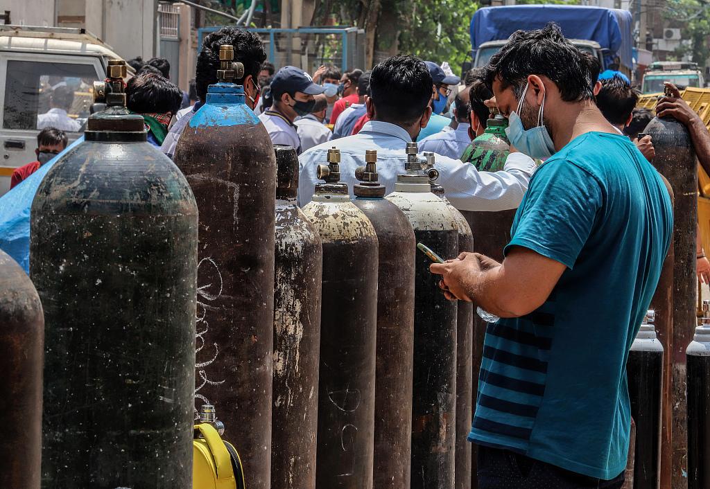资料图:当地时间2021年4月23日,印度新德里,患者家属持空氧气瓶排队等待充氧。(视觉中国)