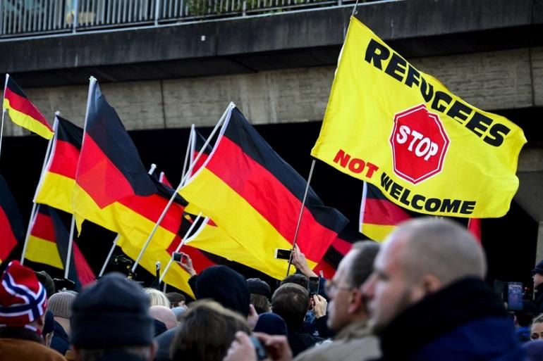 """2017年,德国选择党的支持者举着""""不欢迎难民""""的标语,举行游行。图片来源:半岛电视台"""