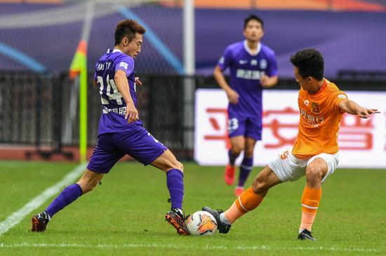 9月28日,天津泰达队球员朴韬宇(左)在竞赛中拼抢。新华社记者李博摄