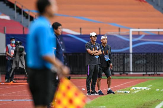 9月28日,天津泰达队主教练王宝山(右二)在场边观战。新华社记者李博摄