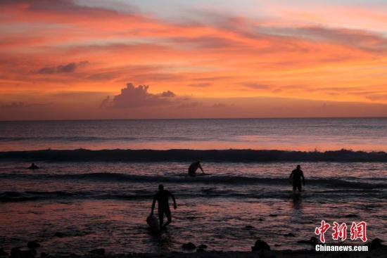 原料图:斜阳西下,在海边的冲浪者。图片来源:视觉中国