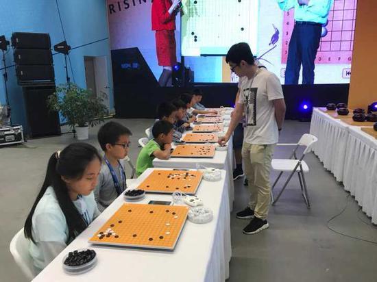中国棋院杭州分院的职业棋手正在与小棋手下指导棋