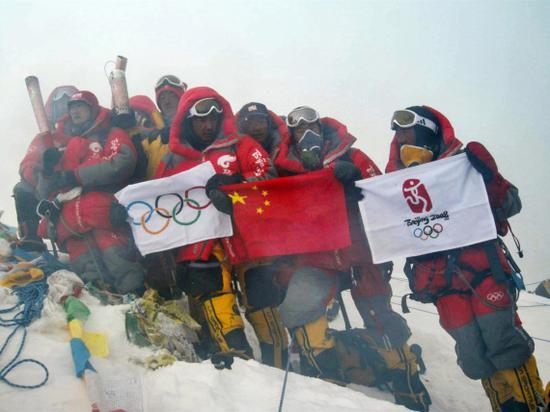 2008年5月8日,北京奥运圣火珠峰传递登山队成功登顶珠峰,中国登山队员在峰顶展示中国国旗、奥运五环旗和北京奥运会会徽旗。新华社发