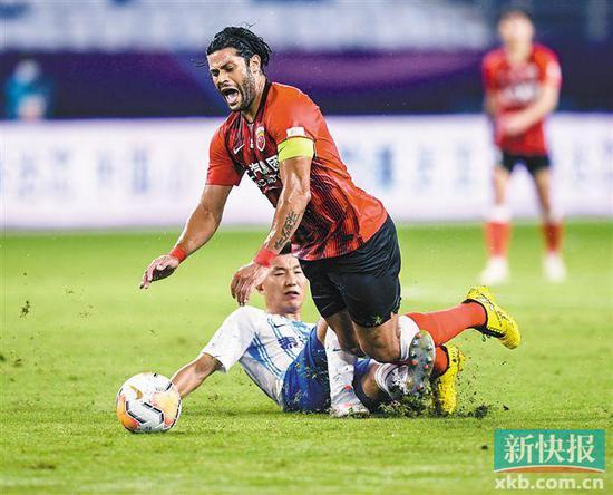 ■上海上港队球员胡尔克(上)被铲倒。新华社发