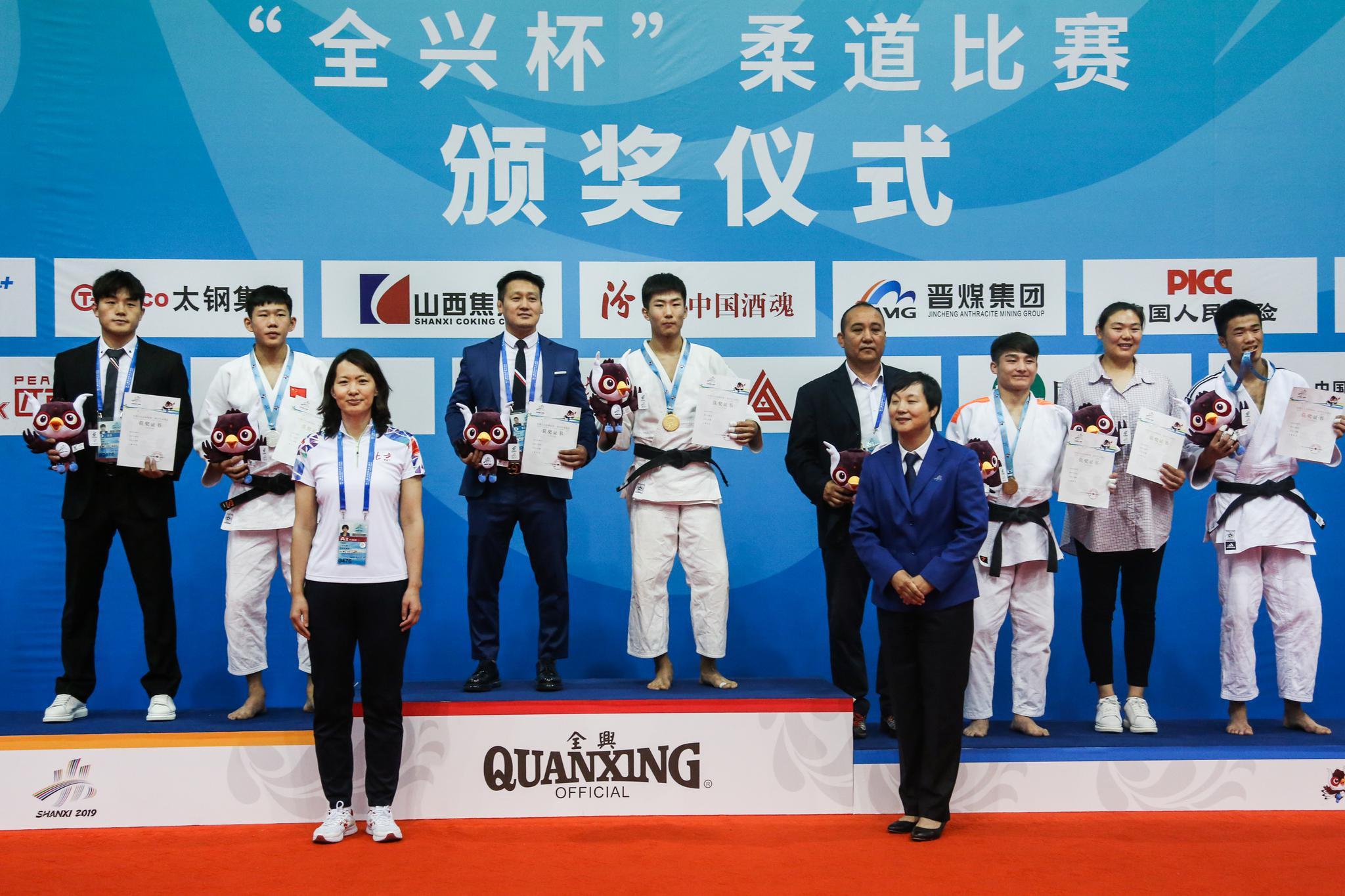 小将苏登和教练一起登上冠军领奖台。北京市体育局供图