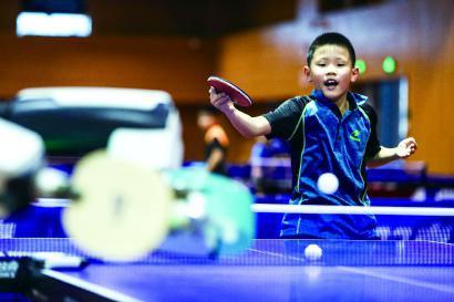 幼球员与中乒院研制的庞伯特众球训练机器人演习 本报记者 李铭珅 摄