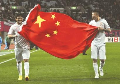 2014年3月11日,亚冠联赛幼组赛山东鲁能客场对阵大阪樱花赛后,洛国富(左)与王永珀挥舞国旗祝贺图新华社