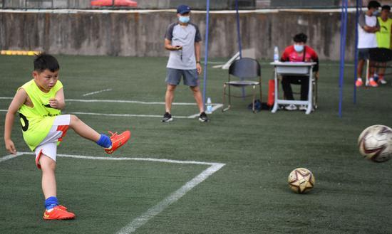 ↑6月17日,参加恒大足球学校入学复试的学生(左一)在参加测试。