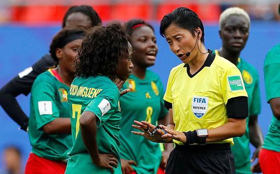 中國主裁秦亮向喀麥隆球員解釋判罰依據。圖/視覺中國