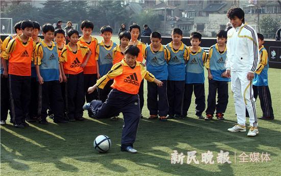 图说:十几年前,郑智辅导幼球员 原料图 周国强 摄