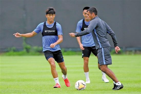 广州富力新帅范布隆克霍斯特(右)请示球员训练