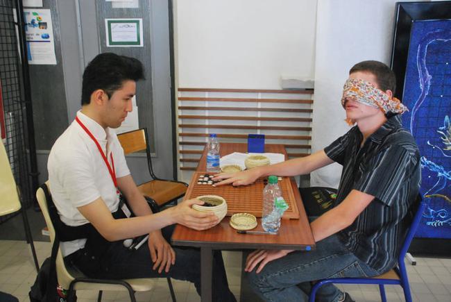日本盲人棋手在围棋大会上,用特制的棋具与人对局。对面的欧洲小伙子也体验盲棋的感觉,两人公平对战。