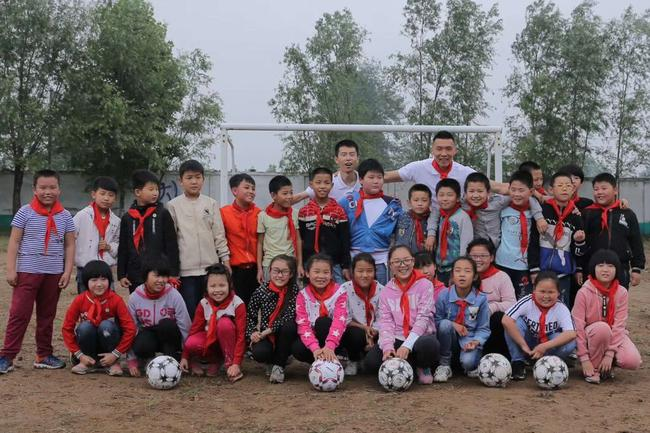 """荆永兴与中国男足队员于大宝(后排右)一路参添""""红粉笔""""公好支教活行。"""