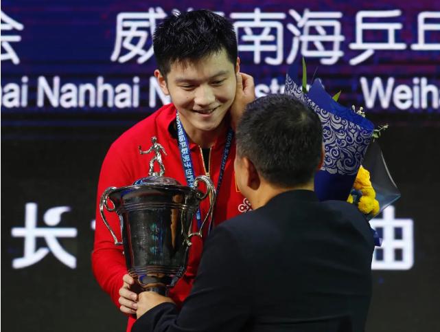 在久违的国际赛场颁奖礼上,刘国梁将奖杯颁发给樊振东。