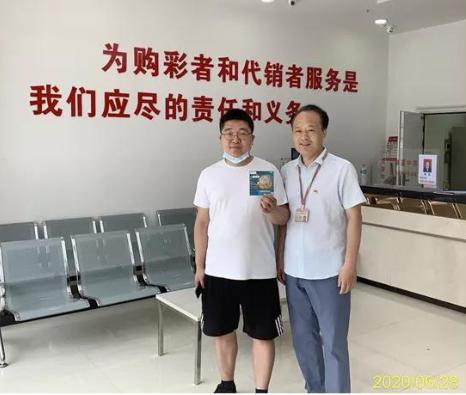 郑州东区分中心主任李文强(右)与中出大奖的实体店出售员相符影