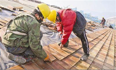 日前,在延庆冬奥村,做事人员在索道A1下站进走屋面木瓦铺设。   任 超摄(新华社发)