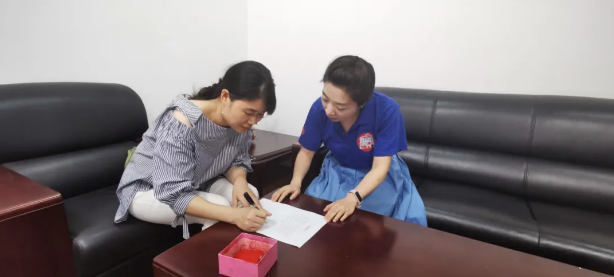 福彩工作人员请大奖站主(左)签署大奖保密协议书