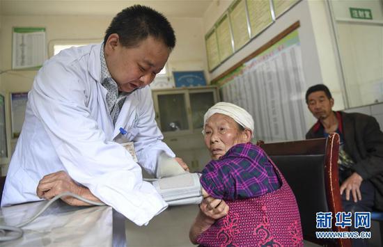 5月28日,何永清(左)在村卫生室为群众诊疗。