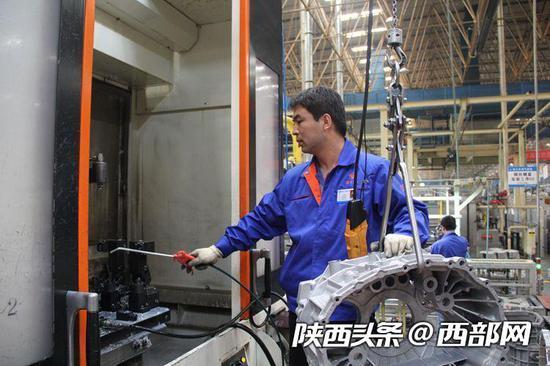 李锋在装卸加工零件。