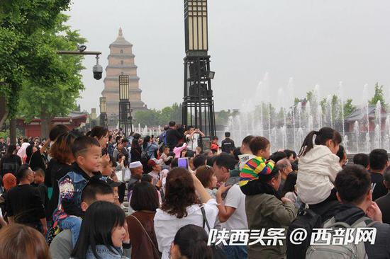 游客在大雁塔广场观看音乐喷泉。