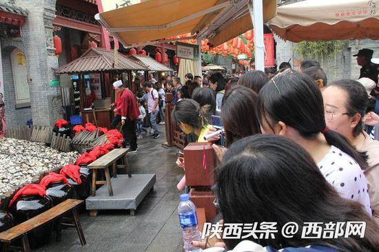 永兴坊景区围观以及排队体验摔碗酒的游客将巷道围得水泄不通。