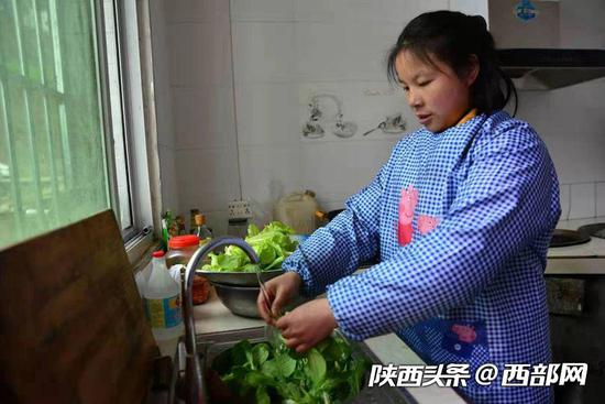 干完农活后,她在家里为一家人做饭。