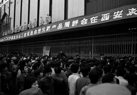1987年,西安永声家电商场门口,市民排队领票购买陕西生产的黄河彩电、长岭冰箱和双鸥洗衣机等。赵康摄