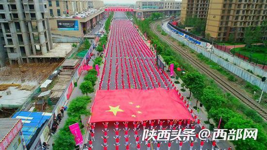 """4000人""""舞动中国""""传递巨幅国旗。"""